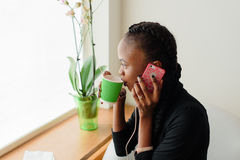 聪明的黑人美国妇女谈话在拿着一次性杯子的电话在窗口旁边 库存图片