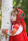 聪明的Sarafan的女孩拥抱桦树 库存照片