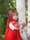 聪明的Sarafan的小女孩拥抱桦树 库存照片