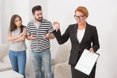 肆无忌惮的租借人争论与房地产经纪商,在她的手保留钥匙和文件 免版税图库摄影