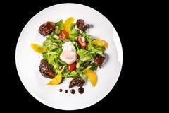 肉、莴苣、桔子、坚果和鸡盘怂恿用在碗的调味汁在黑背景 免版税库存图片