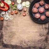 肉丸用草本和葱在一个平底锅用蕃茄、胡椒、夏南瓜和草本在木土气背景顶视图关闭 库存图片