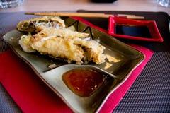 肉卷用在一块板材的辣红色调味汁有筷子和酱油的 库存照片