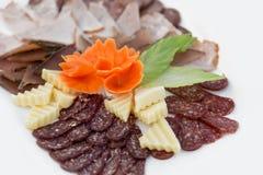 肉和乳酪不同纤巧在轻的背景的一块板材安排了 库存图片
