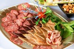肉和乳酪不同纤巧在轻的背景的一块板材安排了 免版税库存图片