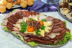 肉和乳酪不同纤巧在轻的背景的一块板材安排了 图库摄影