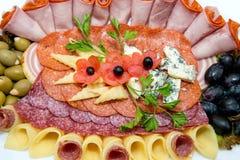 肉和乳酪不同纤巧在轻的背景的一块板材安排了 免版税库存照片
