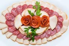 肉和乳酪不同纤巧在轻的背景的一块板材安排了 库存照片