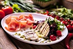 肉和乳酪开胃盘与绿色在木背景 图库摄影