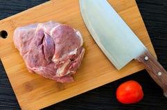 肉和蕃茄在木板 由厨师刀子的切口肉 库存照片