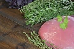 肉和辣草本在木背景 免版税库存照片