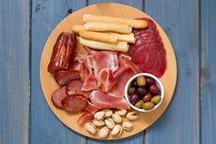 肉开胃菜用橄榄和坚果在盘子在蓝色背景 免版税库存照片