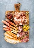 肉开胃菜选择或酒快餐集合 熏制的肉,蒜味咸腊肠,熏火腿,面包条,长方形宝石,橄榄品种  免版税库存图片