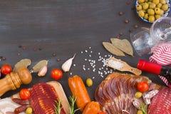 肉开胃菜- jamon、火腿、加调料的口利左香肠、烟肉用新鲜的橄榄,蕃茄、酒和香料在黑暗的木背景 免版税库存图片