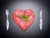 肉心形的未加工的剁  与被绘的利器的肉爱:叉子和刀子 黑暗的黑板背景 免版税库存图片