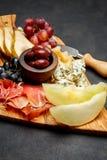 肉板材开胃小菜快餐-意大,青纹干酪,瓜,葡萄,橄榄 图库摄影
