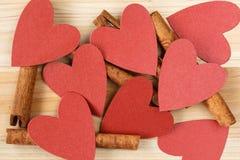肉桂条和红色心脏在木背景 图库摄影