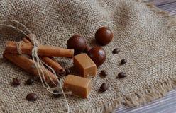 肉桂条栓与串、巧克力糖和咖啡粒是懒惰的在桌上的一块餐巾 免版税图库摄影