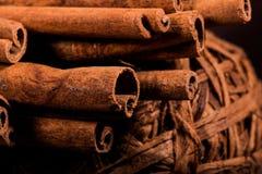 肉桂粉,肉桂条,连接用有一把弓的一个盘子在一个土气样式的颜色背景 宏观照片 免版税库存图片