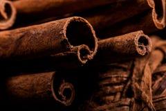 肉桂粉,肉桂条,连接用有一把弓的一个盘子在一个土气样式的颜色背景 宏观照片 库存照片