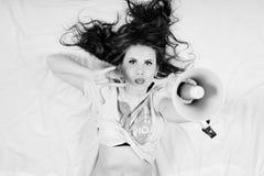 肉欲上放松在轻的拷贝空间的床性感的年轻美丽的妇女的拿着扩音器画象 免版税库存照片