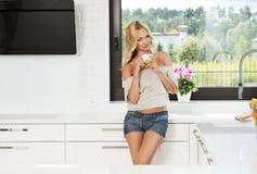 肉欲白肤金发在家喝从杯子 库存照片