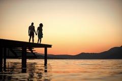 肉欲的夫妇剪影在有日落的码头站立在背景的海表面上 在爱的夫妇在浪漫日期 免版税库存照片