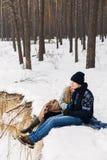肉欲的夫妇在冬天森林里坐在悬崖的毯子 免版税库存照片