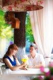 年轻肉欲的夫妇室外画象在夏天咖啡馆的 爱  免版税库存照片