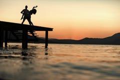 肉欲的夫妇跳舞剪影在码头的有在海表面上的日落的在背景 拉丁文和爱概念 免版税库存图片