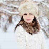 年轻肉欲的女孩在冬天。美好浅黑肤色的男人摆在室外 免版税库存图片