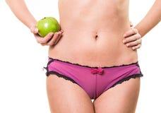 肉欲的女性屁股和苹果在手中 免版税库存图片