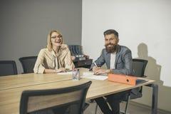 肉欲的妇女和有胡子的人微笑在业务会议上 愉快的女商人和人坐在办公桌 浓度 免版税库存照片