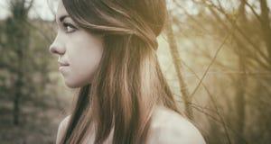 年轻肉欲的妇女在与自然的木和谐中 免版税库存图片