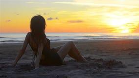 肉欲的妇女松弛获得乐趣在海滩的沙子在日落 股票录像