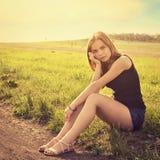 年轻肉欲的微笑的白肤金发的妇女坐草户外 免版税库存图片