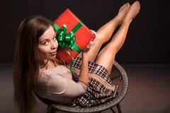 肉欲的性感的可爱的女孩坐一把椅子与 图库摄影