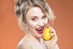 肉欲的性感的白种人白肤金发的女孩尖酸的黄色柠檬果子 摆在反对橙色背景 免版税库存图片