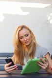 肉欲的愉快的白肤金发的妇女坐长木凳 她使用手机和片剂个人计算机 室外照片 她看起来轻松 免版税库存图片