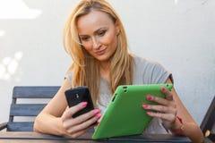 肉欲的愉快的白肤金发的妇女坐长木凳 她使用手机和片剂个人计算机 室外照片 她看起来轻松 库存照片