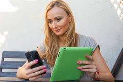 肉欲的愉快的白肤金发的妇女坐长木凳 她使用手机和片剂个人计算机 室外照片 她看起来轻松 免版税库存照片