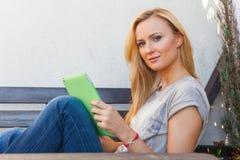 肉欲的愉快的白肤金发的妇女坐长木凳 她使用流动片剂个人计算机 室外照片 她看起来轻松 免版税图库摄影