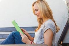 肉欲的愉快的白肤金发的妇女坐长木凳 她使用流动片剂个人计算机 室外照片 她看起来轻松 免版税库存图片