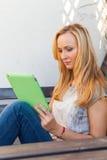 肉欲的愉快的白肤金发的妇女坐长木凳 她使用流动片剂个人计算机 室外照片 她看起来轻松 库存图片