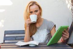 肉欲的愉快的白肤金发的妇女坐长木凳 她使用流动片剂个人计算机 室外照片 她看起来轻松 库存照片