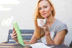 肉欲的愉快的白肤金发的妇女坐长木凳 她使用流动片剂个人计算机 室外照片 她看起来轻松 免版税库存照片