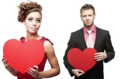 年轻肉欲的拿着在白色的妇女和英俊的人红色心脏 免版税库存照片