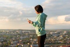 肉欲的年轻亚裔妇女听到在耳机的音乐 被弄脏的城市背景 早晨锻炼概念 免版税库存照片