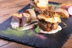 肉热的开胃菜  猪肉和烟肉与绿色 免版税库存照片