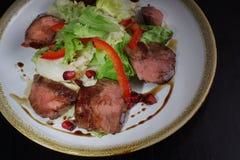 肉热的沙拉用牛里脊肉,冰山沙拉和石榴石装饰用石榴 图库摄影